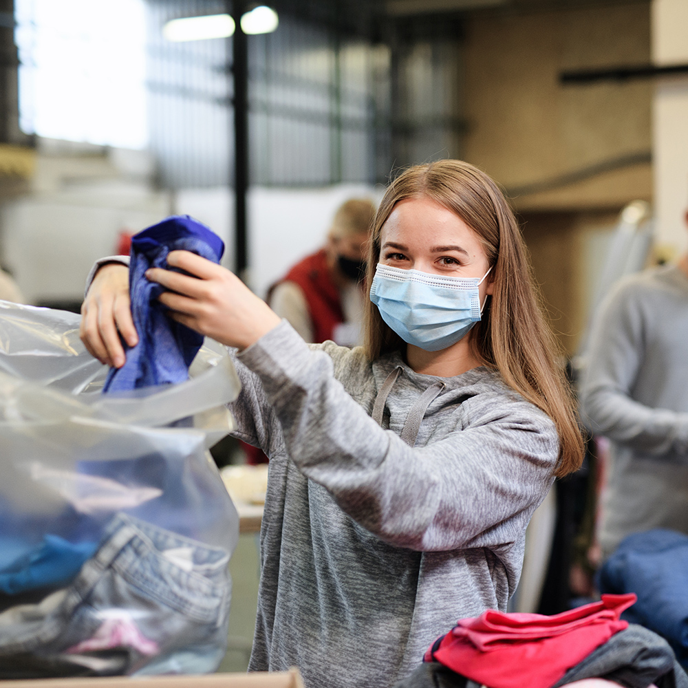 young woman wearing grey top working through clothing charity donations