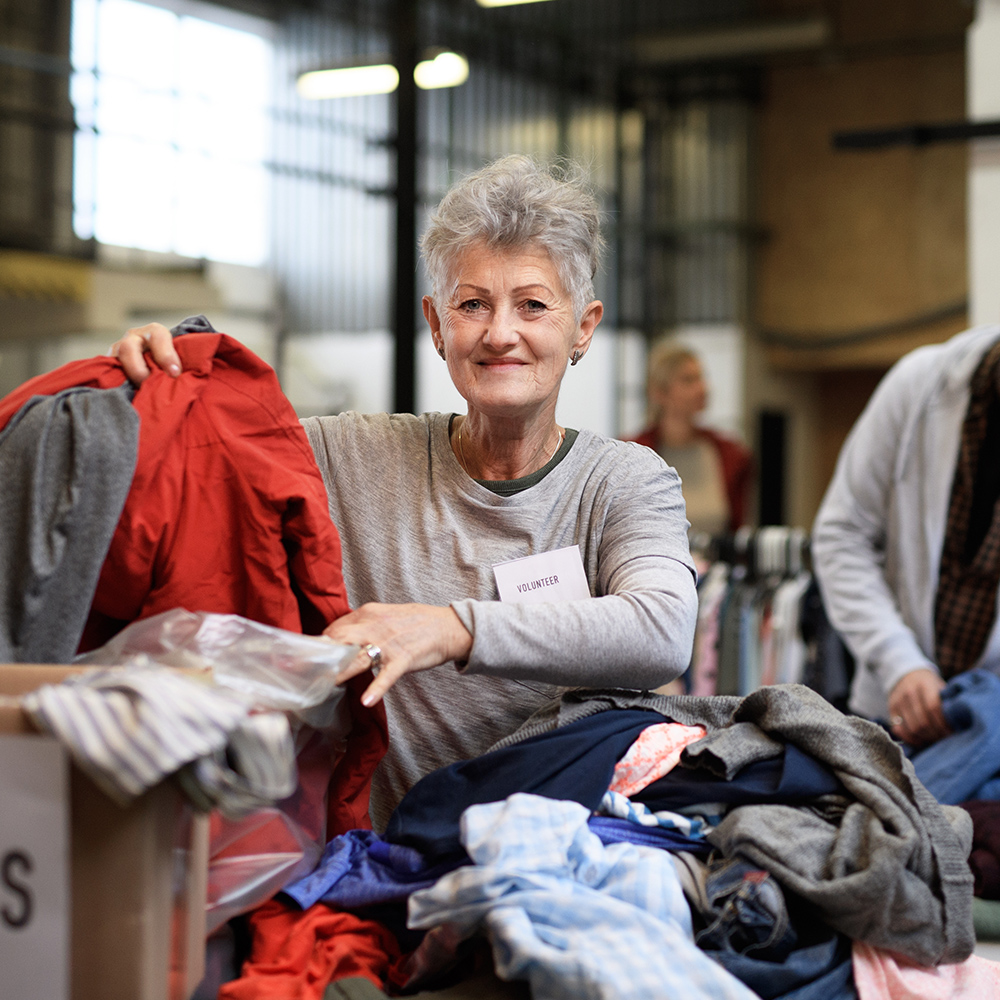 volunteer working through clothing charity donations