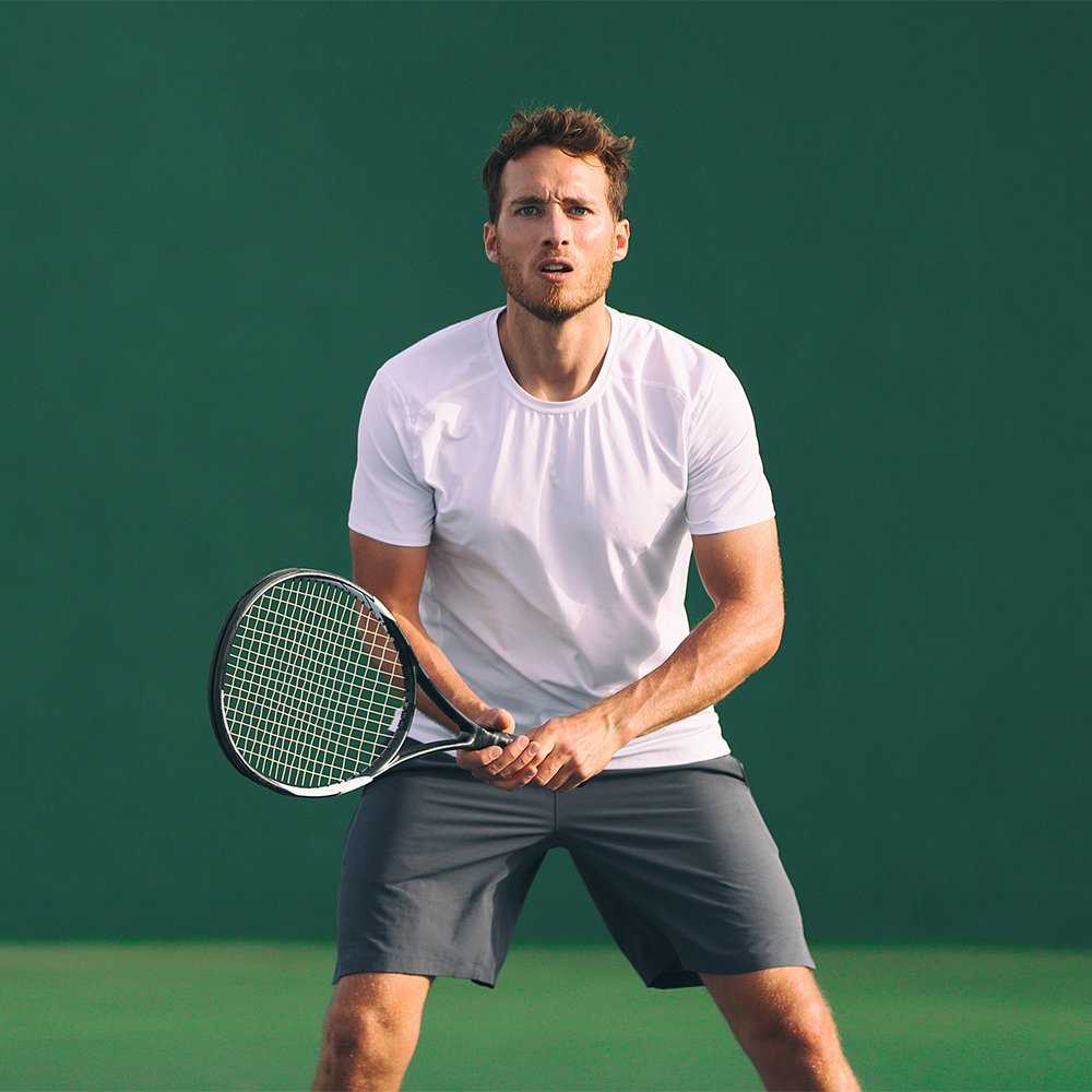 man in white top doing physical exercise as tennis