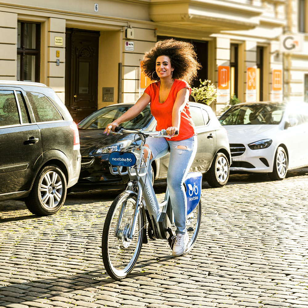 woman in red top and ripped jeans cycling down cobbled road for physical exercise r oad