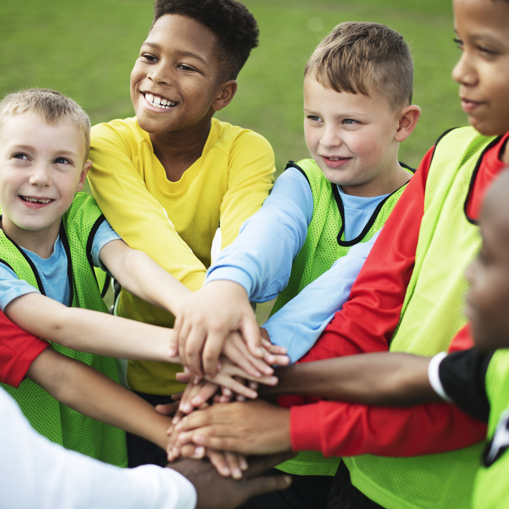 children putting their hands together during a school sports challenge